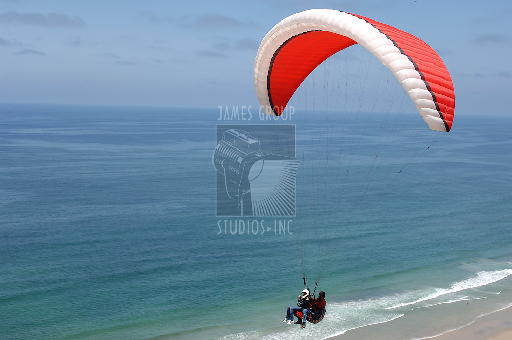 Two people parasailing tandem over the California Coast near San Diego