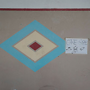 A diamond shaped painting on the wall, from the time when the building was used as a psychiatric clinic, at a now-closed refugee camp at the port of Lakki.<br />