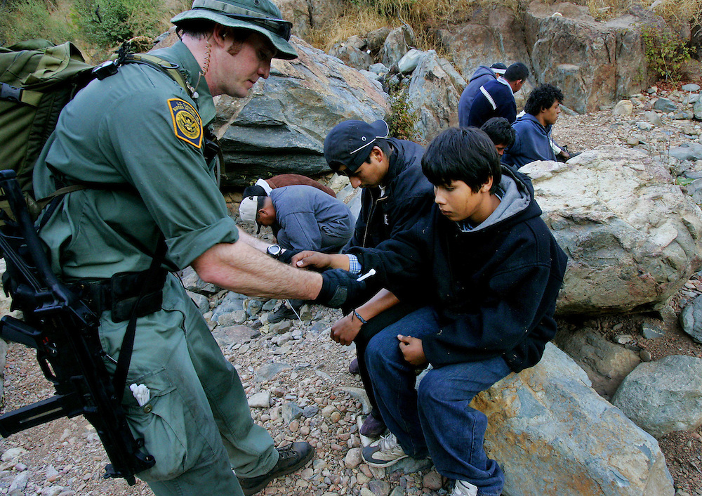 Border patrol agent Jeff Mielke secures plastic handcuff on a group of illegal immigrants caught in the Otay Mesa Mountain Range, just east of San Diego, on Wednesday, October 12, 2005.  Mielke is part of an elite Border Patrol unit that combs remote parts of the border that are unaccessable to vehicles.