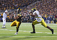 October 10, 2009: Iowa running back Brandon Wegher (3) tries to get around Michigan linebacker Obi Ezeh (45) during the second half of the Iowa Hawkeyes' 30-28 win over the Michigan Wolverine's at Kinnick Stadium in Iowa City, Iowa on October 10, 2009.