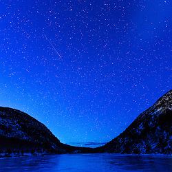 The night sky over The Tarn in Maine's Acadia National Park. Winter.