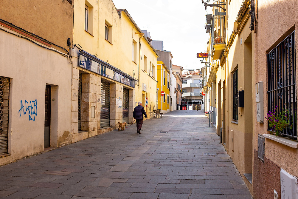 Man walking a dog on Carrer de Sant Antoni on 21 March 2020 - one week into lockdown. Empty streets in Sant Cugat del Valles, a normally bustling city of some 90,000 people outside Barcelona,  a week after Spain exerted a state of Emergency to deal with the spread Coronavirus. Spain is one of the worst affected countries. Schools and retail businesses are closed, except for supermarkets and pharmacies.