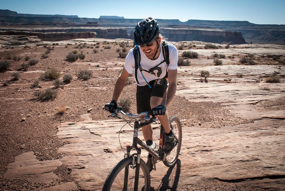 A man in his early thirties mountain bikes the White Rim Trail near Moab, Utah.