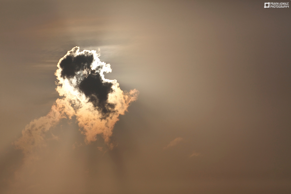 The sun behind the cloud: the glowing golden edges of cloud were so beautyful, created a glowing cloud.