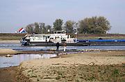 Nederland, the netherlands, Nijmegen, 19-10-2018 Binnenvaartschepen varen in de Waal langs de drooggevallen oever . Door de aanhoudende droogte staat het water in de rijn, ijssel en waal extreem laag . Laagterecord en de laagste officiele stand ooit bij Lobith gemeten . Schepen moeten minder lading innemen om niet te diep te komen . Hierdoor is het drukker in de smallere vaargeul . Door te weinig regenval in het stroomgebied van de rijn is het record verbroken . Foto: Flip Franssen