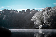 View across lake in IR of dock and boat house