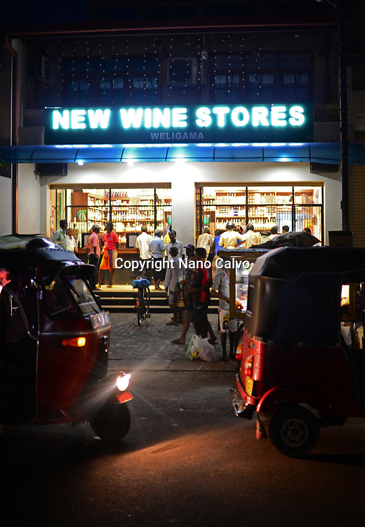 People buying at New wine stores at night in Weligama, Sri Lanka
