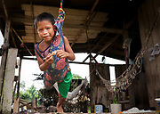 An Embera boy enjoys some of the comforts of modern life in the remote jungle, Churoco, Darien Province, Panama.
