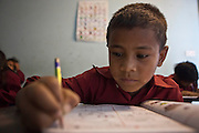 A young Nepalese boy learns to write in his workbook.  He is in a class room at the GoodWeave centre in Attarkhen, Kathmandu, Nepal.  His parents are carpet factory workers, and he has been supported into education by GoodWeave, a charity that works towards getting children out of factories and into education.  Previously these children would have been left unattended in the factory while their parents worked as their low salary could not cover childcare costs. GoodWeave were recipients of the Stars Foundation's Impact Award.