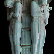 Art Deco light base with male figures holding up outdoor light fixture iin front entrance of building in lower Manhattan.