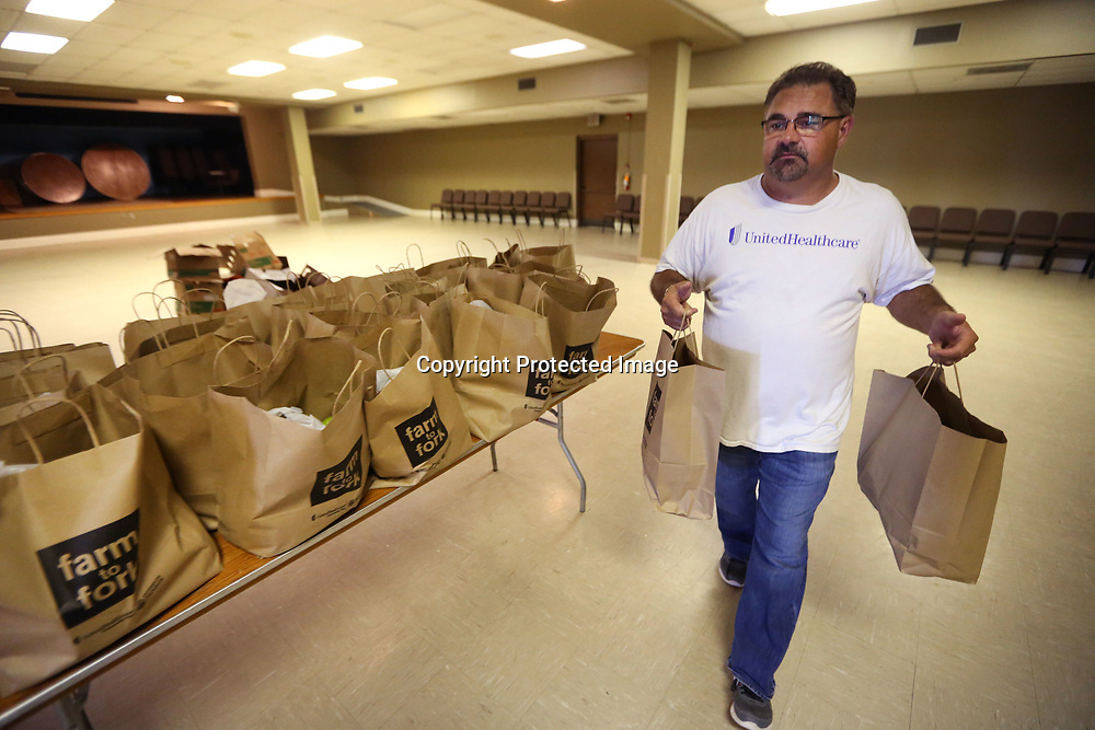 Tommy Adams, with UnitedHealthcare, carries out bags of farm-fresh produce to be picked up by thier plan members. Each summer, UnitedHealthcare Community Plan provides free bags of farm-fresh produce in food desserts throughout the state, to community plan members enrolled in the CHIP and MississippiCAN programs. Bags were distributed Tuesday afternoon at The Link Centre in Tupelo.