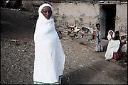 """A woman is a guest at an early marriage's celebration, in which three girls, ages between 3 and 8, are being married. Child marriages are typically made for economic or political reasons. In Ethiopia survives the practice of forced child marriage, even though is forbidden by the law, quite often ignored. North West of Ethiopia, on monday, Febrary 16 2009.....In a tangled mingling of tradition and culture, in the normal place of living, in a laid-back attitude. The background of Ethiopia's """"child brides"""", a country which has the distinction of having highest percentage in the practice of early marriages despite having a law that establishes 18 years as minimum age to get married. Celebrations that last days, their minds clouded by girls cups of tella and the unknown for the future. White bridal veil frame their faces expressive of small defenseless creatures, who at the age ranging from three to twelve years shall be given to young brides men adults already...To protect the identities of the recorded subjects names and specific places are fictional."""