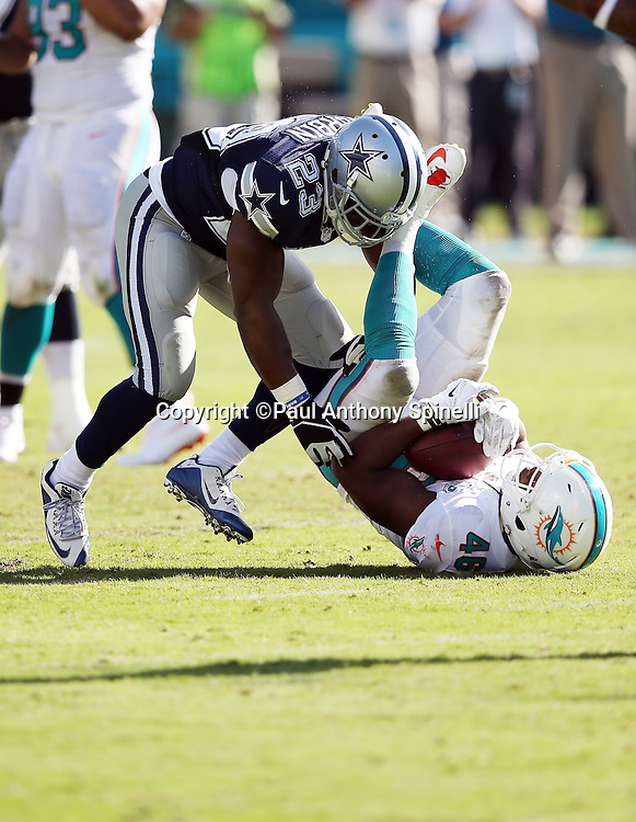 Miami Dolphins linebacker Neville Hewitt (46) gets hit by Dallas Cowboys running back Robert Turbin (23) after intercepting a third quarter pass during the 2015 week 11 regular season NFL football game against the Dallas Cowboys on Sunday, Nov. 22, 2015 in Miami Gardens, Fla. The Cowboys won the game 24-14. (©Paul Anthony Spinelli)