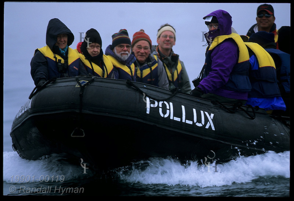 Tourists in rubber raft, or Zodiac, speed across calm waters of Disko Bay; Ilulissat, Greenland