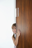 Girl (5-6) peeking from behind door
