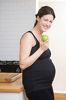 Pregnant woman eating apple in kitchen portrait