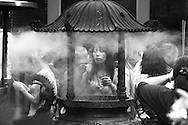A woman places an insence stick in a smokey caldron at Longshan Temple in Taipei, Taiwan.