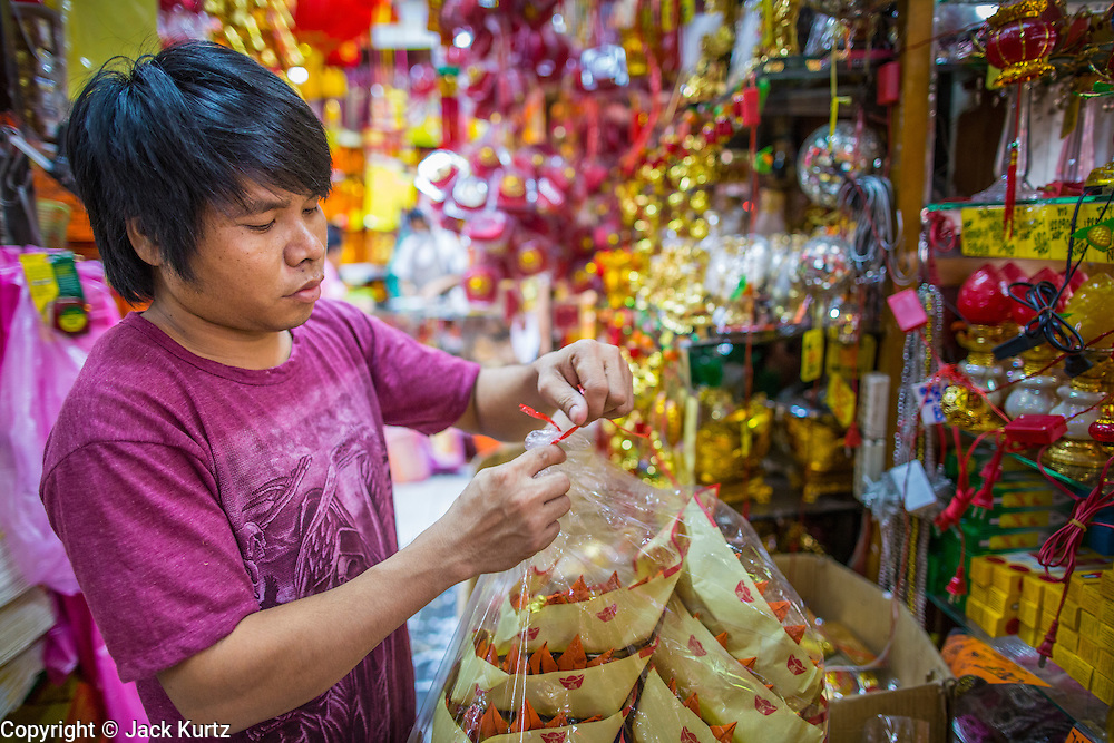 """22 JANUARY 2013 - BANGKOK, THAILAND:   A store employee puts Chinese New Year merchandise on display in a shop on Charoen Krung Road in Bangkok's Chinatown district. Chinese New Year is not an official public holiday in Thailand, but it is one the biggest celebrations in the Bangkok, which has a large Chinese population. Chinese New Year is February 10 this year. It will be the """"Year of the Snake.""""    PHOTO BY JACK KURTZ"""