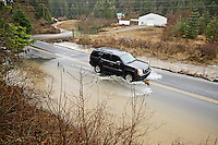A motorist drives through water flowing over Kidd Island Bay Road during a steady rain Friday near Kidd Island Bay.