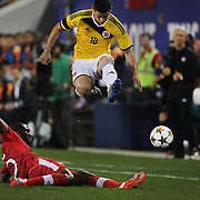 James Rodriguez, Colombia, jumps to avoid the challenge of Doneil Henry, Canada, during the Columbia Vs Canada friendly international football match at Red Bull Arena, Harrison, New Jersey. USA. 14th October 2014. Photo Tim Clayton