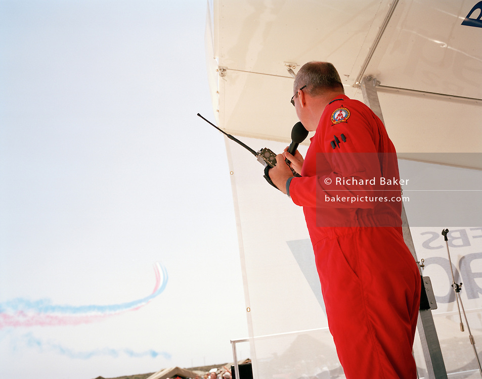 Ground commentator pilot of the Red Arrows, Britain's RAF aerobatic team broadcasts the 30-min display during airshow.