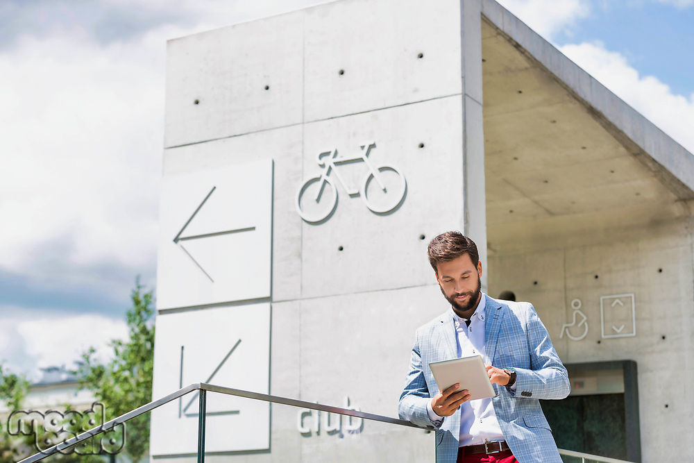 Portrait of young attractive businessman using digital tablet outdoors