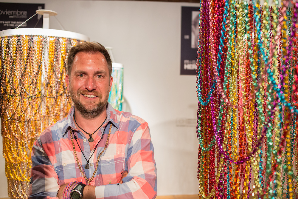 Designer Miguel Herranz of Krisa Decor stands between two pieces in his series Boho-Bling, made of brightly colored chains suspended from hoops, which jiggle when activated by pull strings.