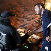 UNCW Assistant Head Soccer Coach Zach Haines shakes hands with David Parrish, father of player Michael Parrish Saturday November 2, 2013 at Carrabba's Italian Grill in Wilmington, N.C. (Jason A. Frizzelle)