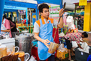 14 OCTOBER 2012 - BANGKOK, THAILAND:  An iced coffee vendor puts on a show while he makes a cup of vegan iced coffee on the first day of the Vegetarian Festival on Yaowarat Road in Bangkok's Chinatown. The Vegetarian Festival is celebrated throughout Thailand. It is the Thai version of the The Nine Emperor Gods Festival, a nine-day Taoist celebration beginning on the eve of 9th lunar month of the Chinese calendar. During a period of nine days, those who are participating in the festival dress all in white and abstain from eating meat, poultry, seafood, and dairy products. Vendors and proprietors of restaurants indicate that vegetarian food is for sale by putting a yellow flag out with Thai characters for meatless written on it in red.    PHOTO BY JACK KURTZ