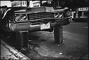 A New York Cadillac up on bricks after it's wheels have been stolen, New York, USA, 1980