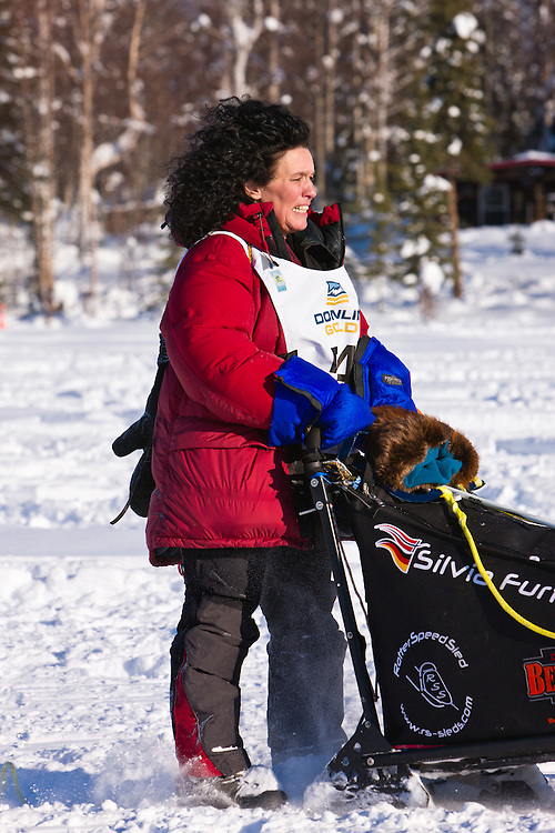 Musher Silvia Furtwangler competing in the 40th Iditarod Trail Sled Dog Race on Long Lake after leaving the Willow Lake area at the restart in Southcentral Alaska. Afternoon. Winter.