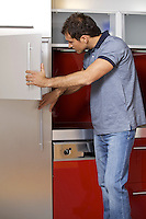 Young man looking in refrigerator
