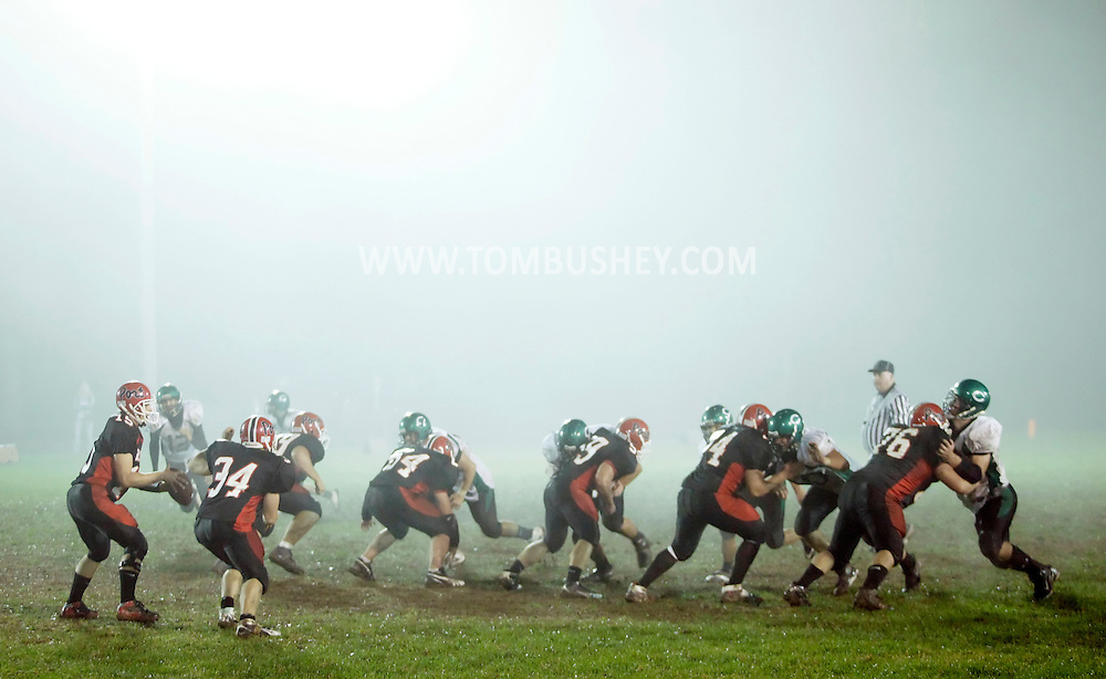 Port Jervis quarterback Chris Stawski, far left, takes the snap against Cornwall in the fog on Friday, Oct. 9, 2009.