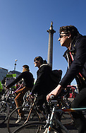 Cyclists pass Trafalgar Square during the Time To Act, National Climate March organised by Campaign Against Climate Change in London, England on March 7, 2015