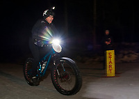 Kale Poland cheers Mike Baron on as he finishes the Fatbike Fury night race at Gunstock Nordic on Saturday evening.  (Karen Bobotas/for the Laconia Daily Sun)