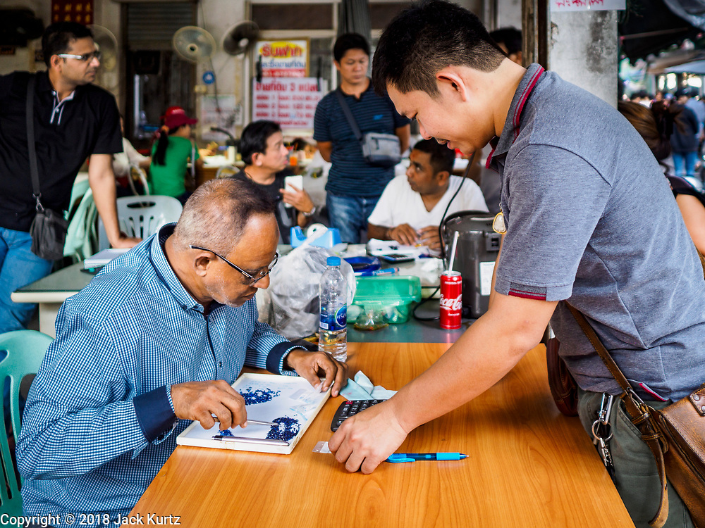 21 DECEMBER 2018 - CHANTABURI, THAILAND: A customer (right) talks to a gem merchant in the gem market in Chantaburi. The gem market in Chantaburi, a provincial town in eastern Thailand, is open on weekends. Chantaburi used to be an active gem mining area in Thailand, but the mines are played out now. Now buyers and sellers come from around the world to Chantaburi for the weekend market. Many of the stones come from Myanmar, others come from mines in Afghanistan and Africa.       PHOTO BY JACK KURTZ