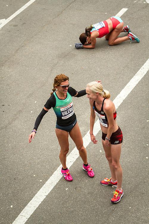 ING New York CIty Marathon: elite runners Valeria Straneo congratulates Kim Smith as Sabrina Mockenhaupt kneels