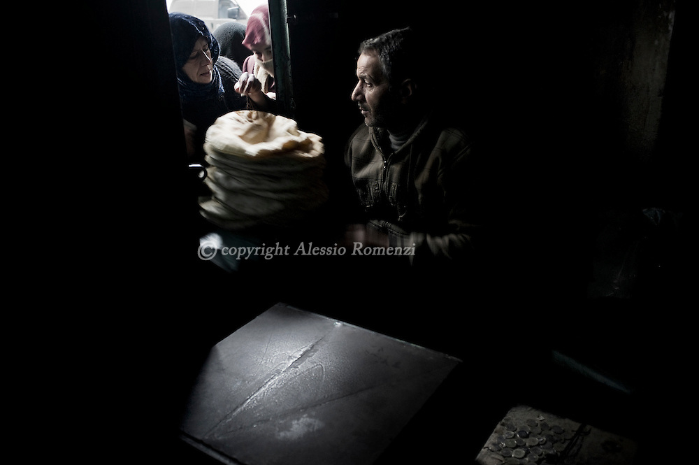 SYRIA - Al Qsair. A woman buy some bread in of one of the three groceries in Al Qsair, on January 24, 2012. Al Qsair is a small town of 40000 inhabitants, located 25Km south-west of Homs. The town is besieged since the beginning of November and so far it counts 65 dead. ALESSIO ROMENZI