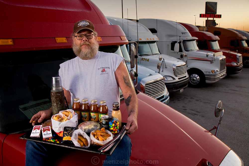 USA  The Long Haul Trucker.Conrad Tolby, an American long-distance truck driver, photographed with a typical day's worth of food on the cab hood of his semi tractor trailer at the Flying J truck stop in Effingham, Illinois. The caloric value of his meals this working weekday was 5,400 kcals. At the time of the photograph Tolby was 54 years of age; 6 feet, 2 inches tall; and weighed 260 pounds. His meals on the road haven't changed much over the years?truck stop and fast-food fare, heavy on the grease?despite warnings from his doctor. He has more reason than most to watch his diet, as he's suffered two heart attacks?both in the cab of his truck. The trucker travels with his best friend and constant companion, a five-year-old shar pei dog, named Imperial Fancy Pants, who gets his own McDonald's burger and splits the fries with Conrad. From the book What I Eat: Around the World in 80 Diets. (Please note that the calorie total is not a daily caloric average. See his chapter, and the methodology, in the book for more information). MODEL RELEASED...Note: The authors used a typical recent day as a starting point for their interviews with 80 people in 30 countries. They specifically chose not to cover daily caloric averages, as they wanted to include some extreme examples of eating, like one woman's diet on a bingeing day or the small number of calories a herder in Kenya ate during extreme drought. The texts in the book provide the context for the photographs, detailing each person's diet, culture, and circumstance at the moment they were photographed: a snapshot in time. A complete methodology is available in the book.