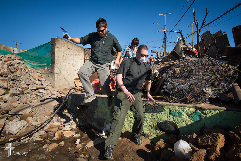 (L-R) The Rev. Cristian E. Rautenberg, president of the Confessional Lutheran Church of Chile and the Rev. Michael Meyer, manager of LCMS Disaster Response, jump through debris as they visit victims from a devastating fire in Valparaíso, Chile, on Monday, April 21, 2014. The catastrophic fire that tore through the hillsides above the historic port city fire killed 15 people, destroyed about 3000 homes, and left approximately 15,000 people homeless.  LCMS Communications/Erik M. Lunsford