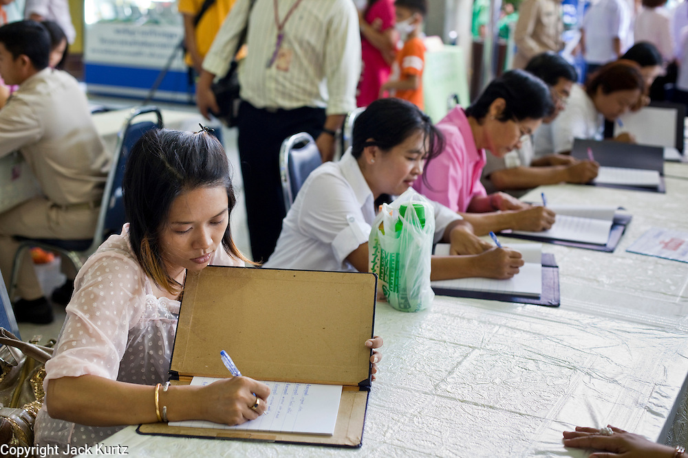 Sept. 22, 2009 -- BANGKOK, THAILAND: People sign get well cards in the lobby of Siriraj Hospital for King Bhumibol Adulyadej, the 81-year-old King of Thailand. The King has been admitted to hospital suffering from a fever. Doctors at Siriraj Hospital said the world's longest-serving monarch, had shown signs of fatigue and was being treated with antibiotics. King Bhumibol is deeply revered by most Thais and his health is a matter of public anxiety. His Majesty was admitted on Saturday suffering from a fever, fatigue and loss of appetite. Doctors continued to treat the King with intravenous drips and antibiotics, hospital officials said. More than 3,500 people have come to the hospital to pray for the King's speedy recovery and to sign get well cards for him.  Photo by Jack Kurtz