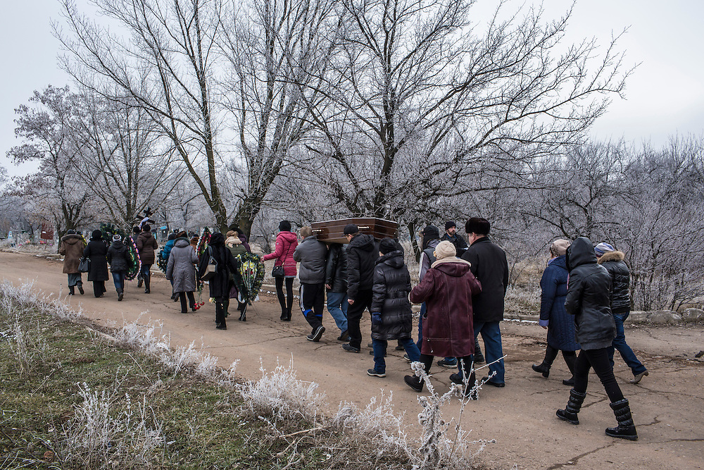 ARTEMIVSK, UKRAINE - FEBRUARY 15: Family and friends carry the casket of Igor Molodetskykh, 7, who was killed two days prior when a shell hit his school on February 15, 2015 in Artemivsk, Ukraine. A ceasefire scheduled to go into effect at midnight was reportedly observed along most of the front, save for near the embattled town of Debaltseve. (Photo by Brendan Hoffman/Getty Images) *** Local Caption *** Zhanna Molodetskykh