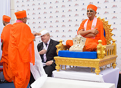 Image ©Licensed to i-Images Picture Agency. 28/05/2014. London, United Kingdom. Boris Johnson visits Hindu Temple, Kingsbury  visit. . Picture by Fiona Hanson / i-Images<br /> <br /> <br /> 20140528Copyright image 2014 Mayor of London, Boris Johnson visits a new Hindu templex complex, Shree Swaminarayan Mandir Kingsbury, north London. During the visit he was fitted with a traditional turban, a garland and marked with the tilak chandlo on his forehead by the denomination's spiritual leader, Acharya Swamishree Maharaji. The under-construction temple is due to replace the current temple in Golders Green in August.<br /> <br /> <br /> For further information please contact Fiona Hanson on 07710 142633 or email info@fionahanson.com