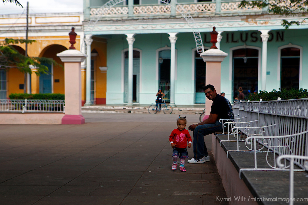 Central America, Cuba, Remedios. Father watches as toddler takes steps in park in Remedios.