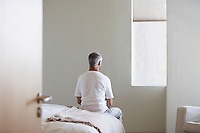 Man sitting on edge of bed back view