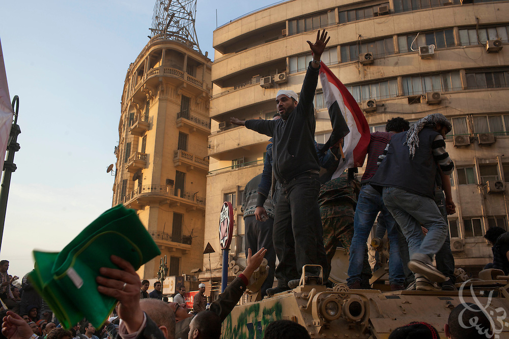 An Anti-Mubarak protester rallies other protesters from atop an Egyptian Army personnel carrier to help defend their line against pro-Mubarak protesters on the edge of Tahrir Square February 02, 2011in Cairo Egypt. Both sides faced off today, battling for control of the square which has been at the center of more than a week of ongoing protests across Egypt. As night fell, there are reports that the Army has ordered everyone in the square to evacuate. .Slug: Egypt