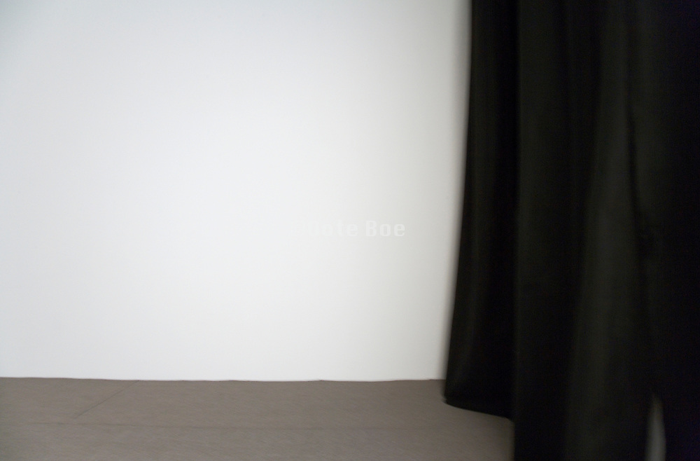 detail of black curtain against a white wall with light camera motion blur