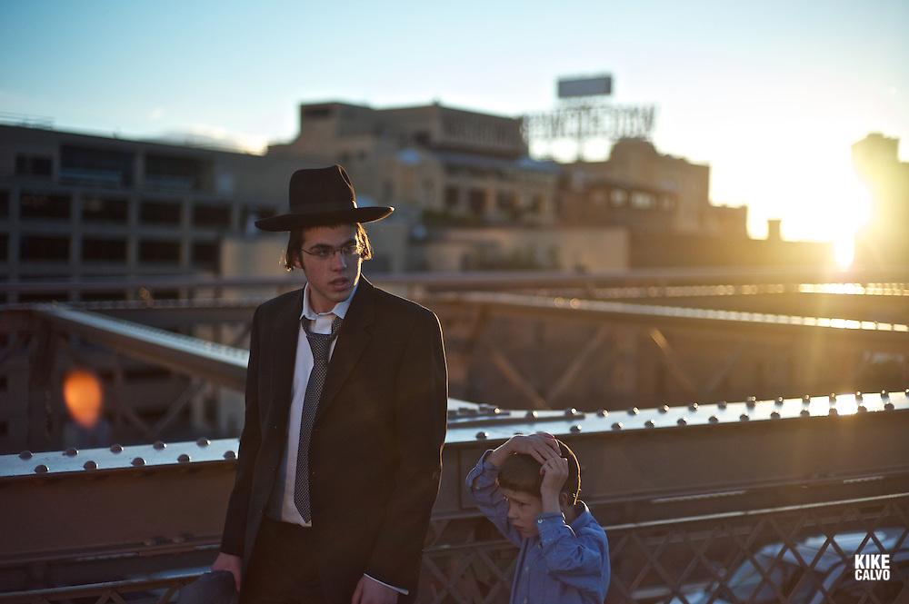 Brooklyn Bridge  Orthodox Jewish, father and son, walking on the Brooklyn Bridge at sunset