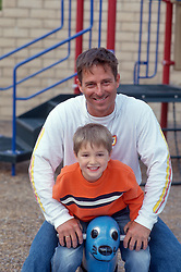 man and boy on a playground ride