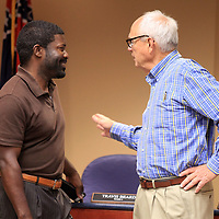 Aaron Washington, a member of the police advisory board member, talks with Travis Beard, Tupelo Ward 3 Councilman, inside council chambers at Tuesday nights city council meeting.